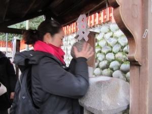 重軽石を持ち上げる観光客