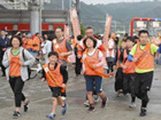 大津港を出発するびわ湖一周オレンジリボンたすきリレー の参加者