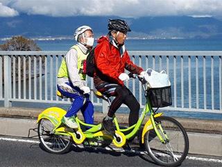 タンデム自転車で琵琶湖岸を走る平岡行雄さんと山野勝美さん