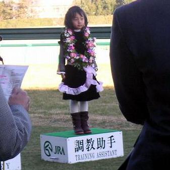 テイエムプリキュアの表彰式にプリキュアの衣装で調教助手台に立つ女の子
