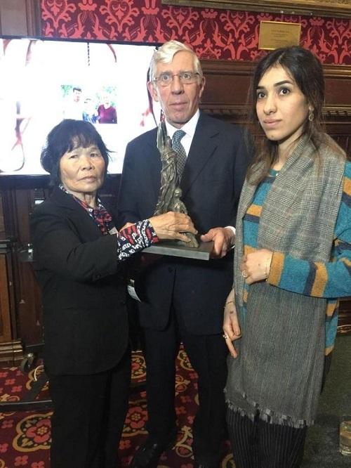 16日、英議会ストレンジャー・ダイニングルームで開かれた韓国のベトナム戦争性犯罪「ライダイハン」問題を追及する集会でライダイハン像を持つストロー元英外相(中央)と、ノーベル平和賞受賞者、ナディア・ムラ