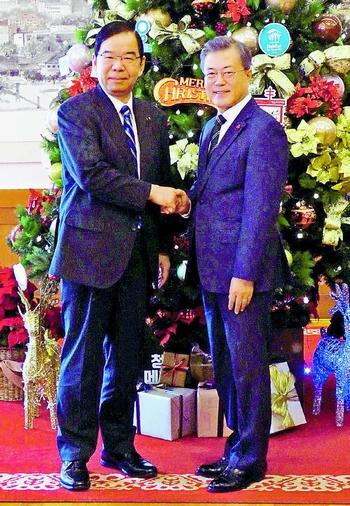 写真)韓国大統領府で会談後、文在寅大統領(右)と握手する志位委員長=14日、ソウル