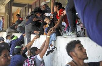警察から逃れて米国との国境近くの壁をよじ登る移民たち=メキシコ北西部ティフアナで25日、ロイター