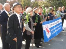 ヒバクシャ地球一周 証言の航海-広島平和祈念公園をバナーを持ち行進