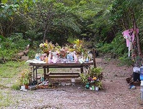 米軍属女性暴行殺人事件で、被害者の遺体が遺棄された現場。献花台には新しい花やペットボトルなどが並んでいる=9月20日、恩納村安富祖