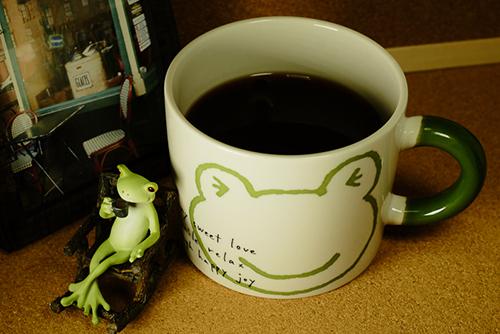 ツバキアキラが撮ったカエルのコポー。コーヒーがなみなみとつがれた、カエルさんのマグカップの隣で、コーヒーを飲むコポタロウ。