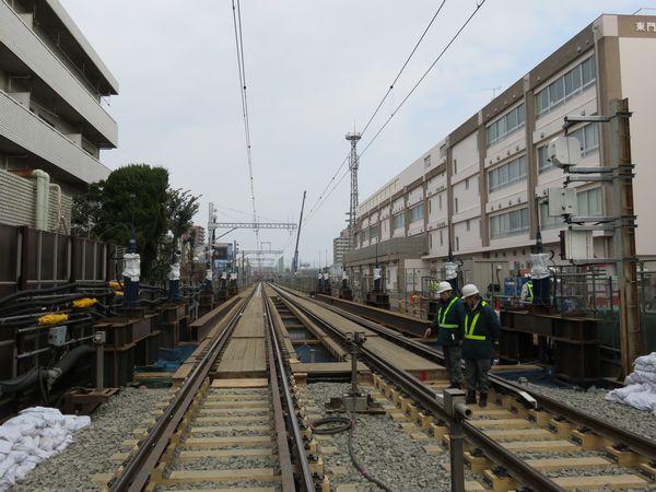 東門前駅前の踏切から産業道路駅方向を見る。線路脇には桁を降下させるためのジャッキが設置されている。