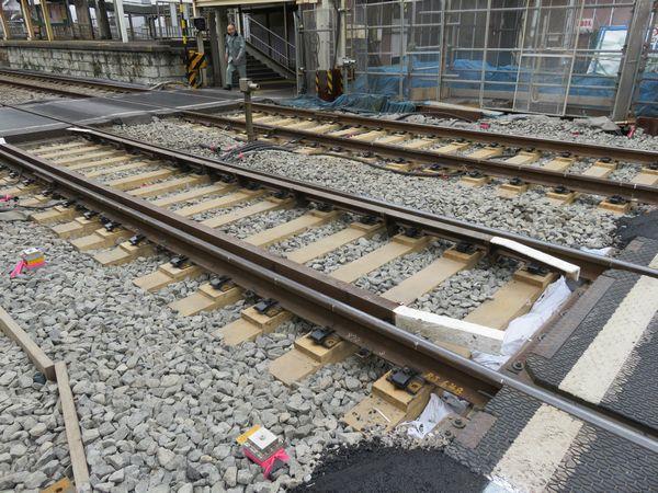 東門前駅前の踏切周辺の線路。枕木とレールの間に木片が挿入されており、地下化時にこれを取り去り線路の高さを下げる。